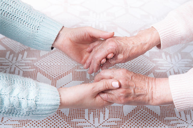 Care is at home of elderly. Senior woman with their caregiver at home. Concept of health care for elderly old people. Disabled. Elderly woman holding hands stock photography