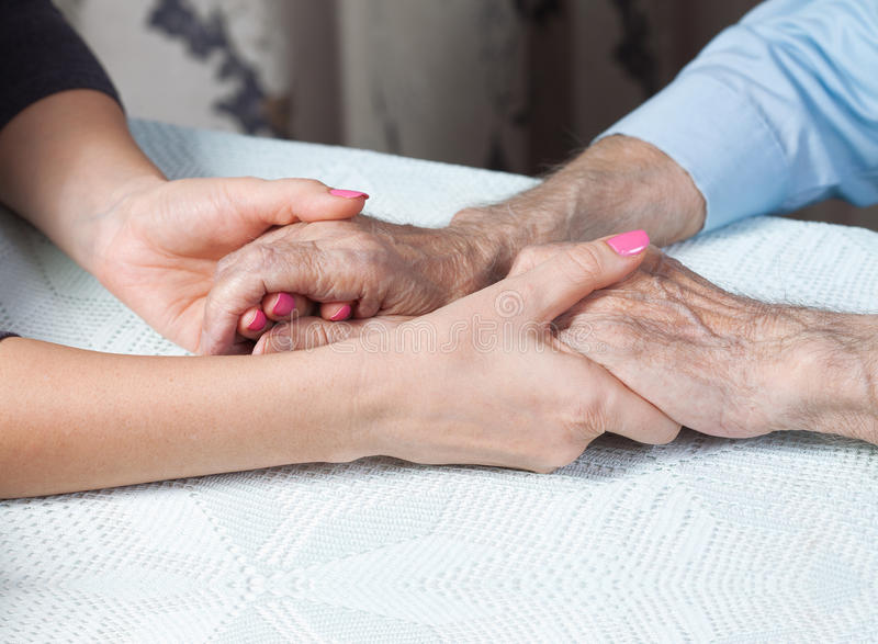 Care is at home of elderly. Space for text. Senior man, woman with their caregiver at home. Concept of health care for elderly old people, disabled. Elderly royalty free stock photo