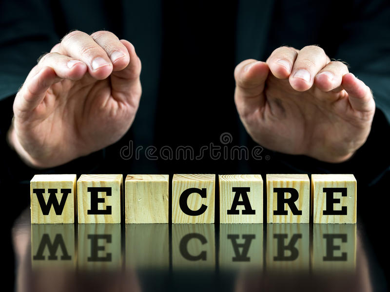 We care. Man holding his hands protectively over words We care on a row of wooden cubes in a conceptual image, closeup of the cubes and hands royalty free stock images