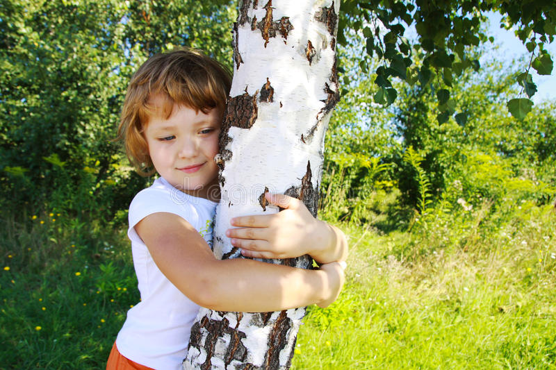 Care for nature - little girl embrace a tree