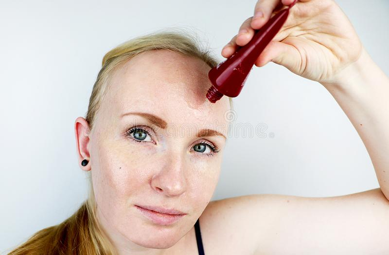 A young woman puts a gel mask on her face. Care for oily, problem skin stock images