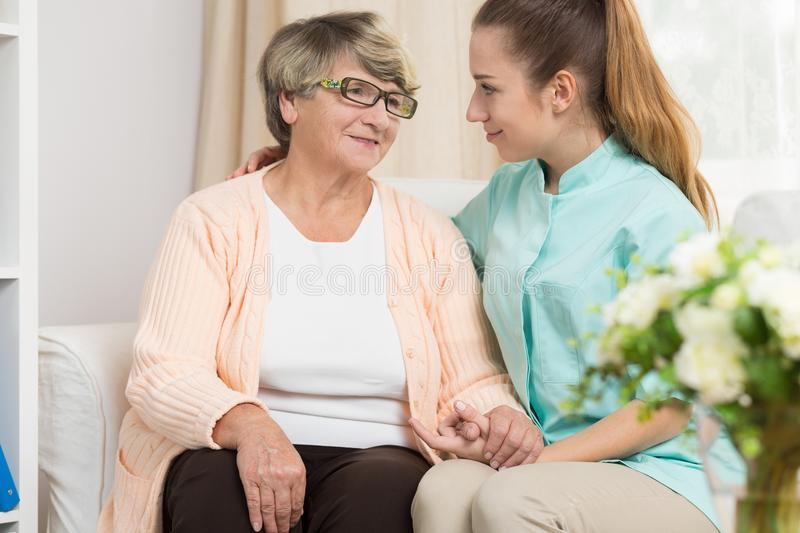 Care and support in rest home. Young caregiver providing care and support in rest home stock photography