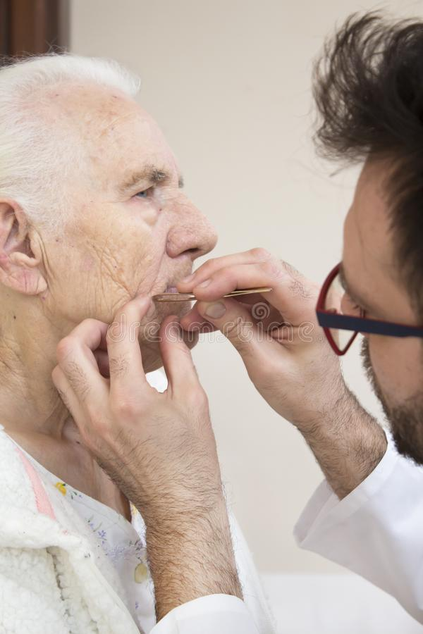 Care treatments on the face of an old woman. Removing facial hair with tweezers. royalty free stock photos