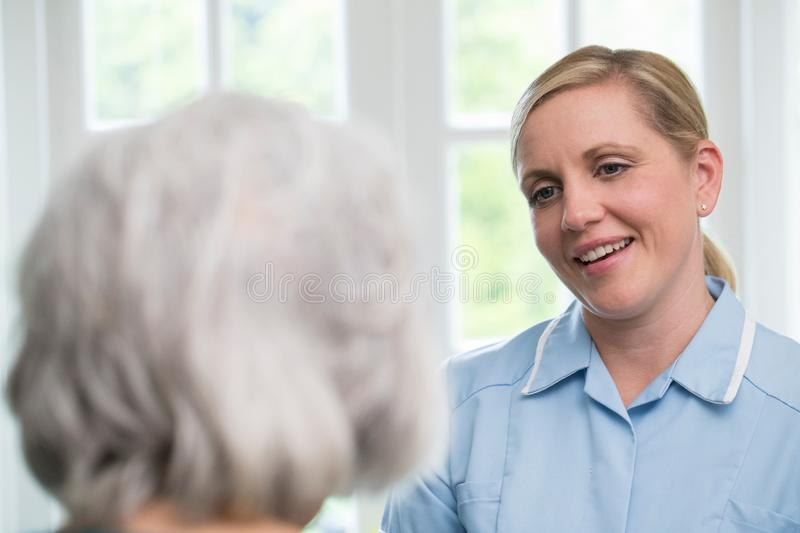 Care Worker Talking To Senior Woman At Home royalty free stock images