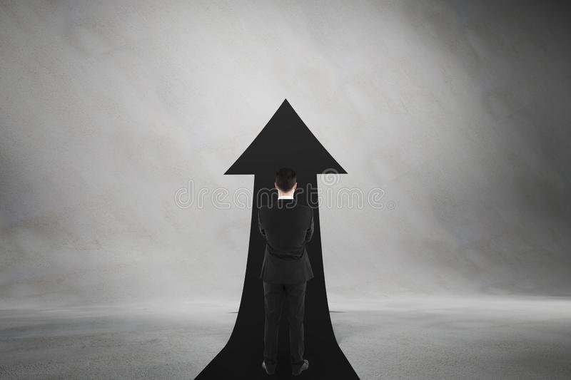 Career advancement concept with businessman staying midst black upward road-arrow royalty free stock images