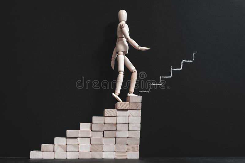 Career aspiration wooden man climbing stairs chalk stock image