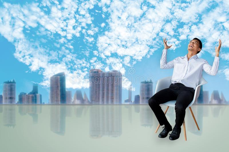 Career business man sitting chair Express feeling In gray room and sky with city blurry background Metaphor for Success finance De stock images