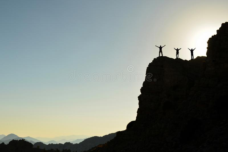 Mountain Climber Silhouettes Symbolizing Career Climbers  royalty free stock photography