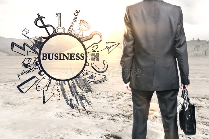 Career concept. Back view of businessman with briefcase in abstract desert with creative business sketch. Career concept royalty free stock photos