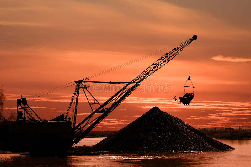 Career dredge. Silhouette of a career dredge on a background of an evening dawn royalty free stock photos