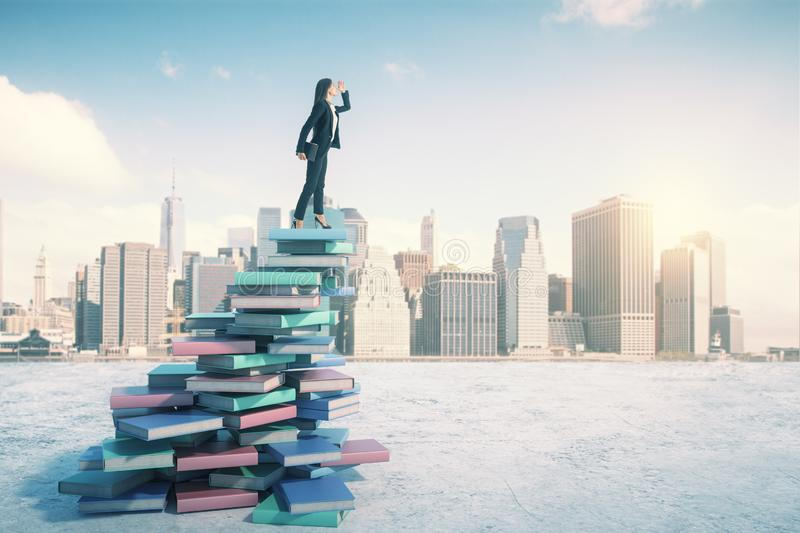 Career and education concept with businesswoman on book mountain looking into the distance. At city skyline royalty free stock images