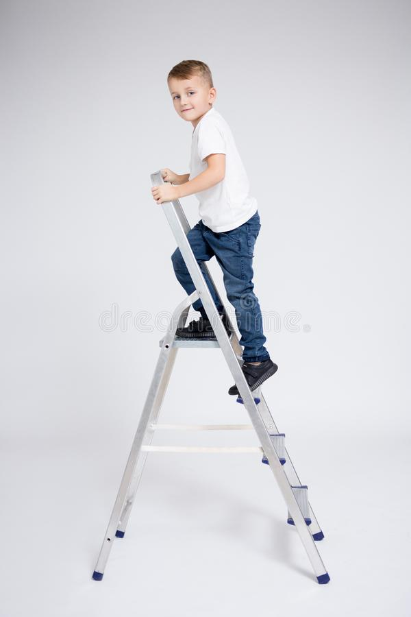 Career and education concept - little boy on stepladder over white background stock photos