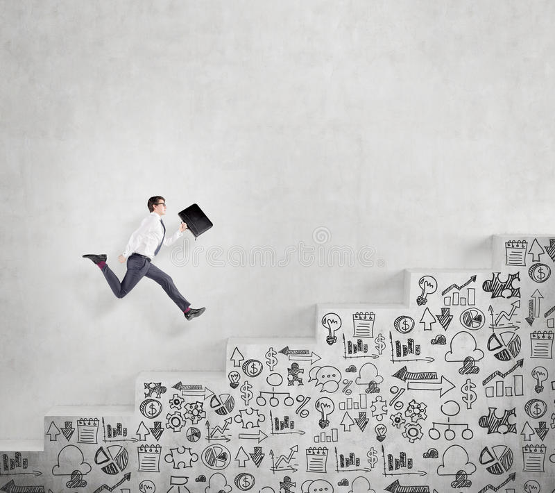 Career growth. Young businessman with a folder running fast up a a concrete stairs with drawn business icons on it along a concrete wall. Concept of career stock photos