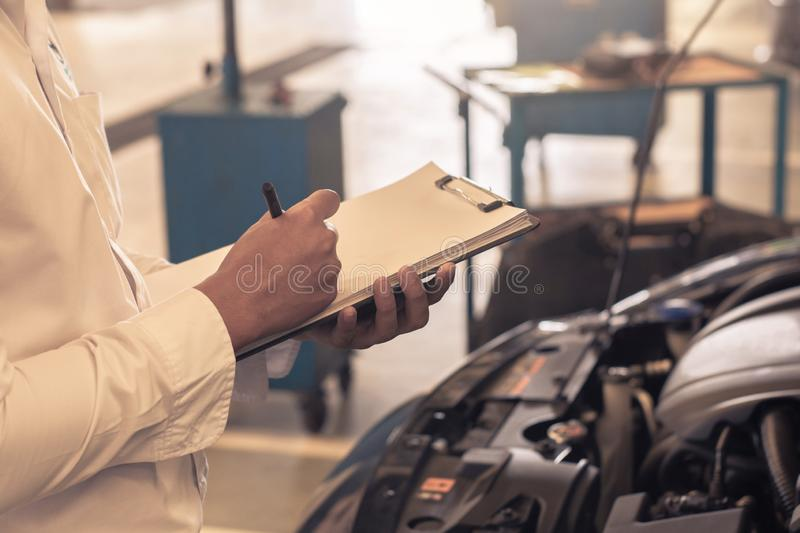This career man saleman business inspection writing note on notepad or book, paper with car blurry background.for transport automo royalty free stock photography