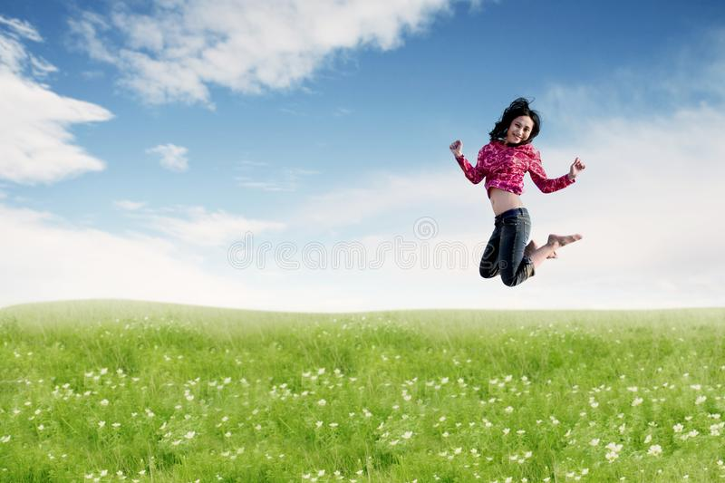 Carefree Asian woman making a big jump on meadow. royalty free stock photo