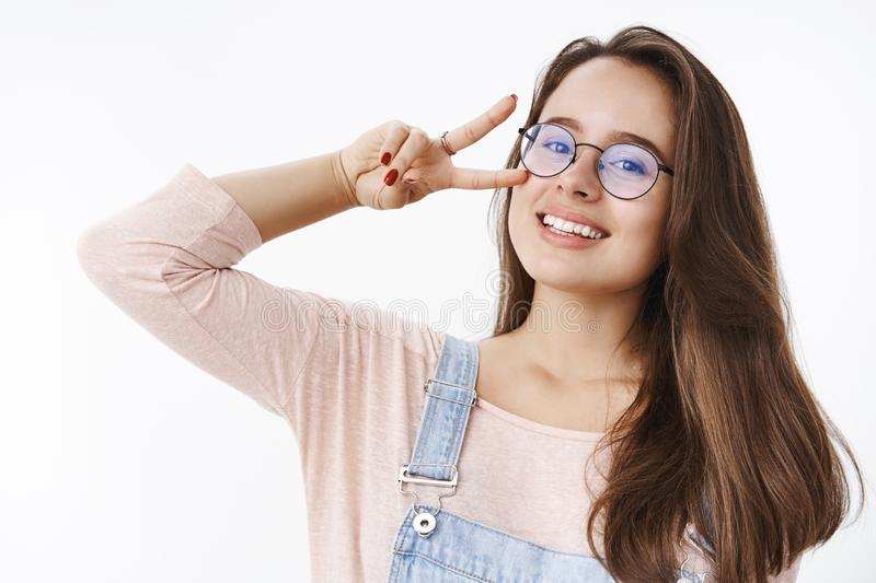 Carefree attactive young charismatic 20s woman in glasses with brown hair showing victory or peace gesture near face stock images