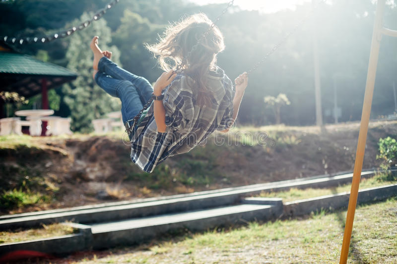 Carefree barefoot girl on swing in sun light stock image