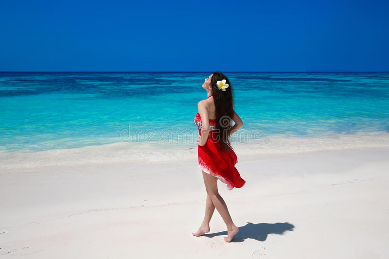Carefree beautiful woman enjoying on the exotic sea. Happy brunette girl in red dress relax on tropical beach island. Summer royalty free stock photos