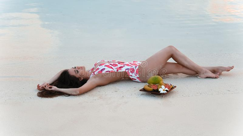 Carefree brunette woman lying on white sand Enjoying life on Tropical Beach. Sexy bikini model with exotic fruits stock photography