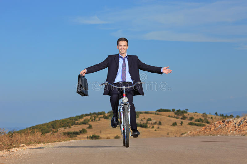 Carefree Businessman Riding A Bicycle Royalty Free Stock Image
