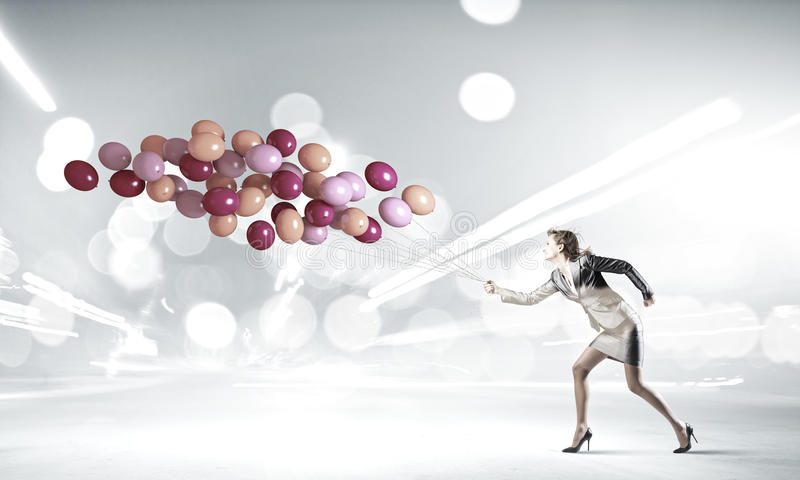 Carefree businesswoman. Young businesswoman with bunch of balloons running in a hurry royalty free stock images