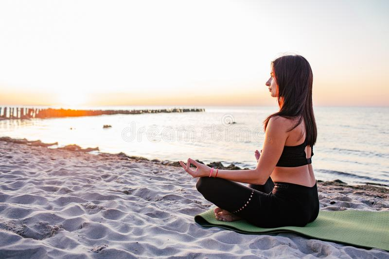 Carefree calm slim woman meditating in nature and practice Yoga on a beach with sunset background royalty free stock photography