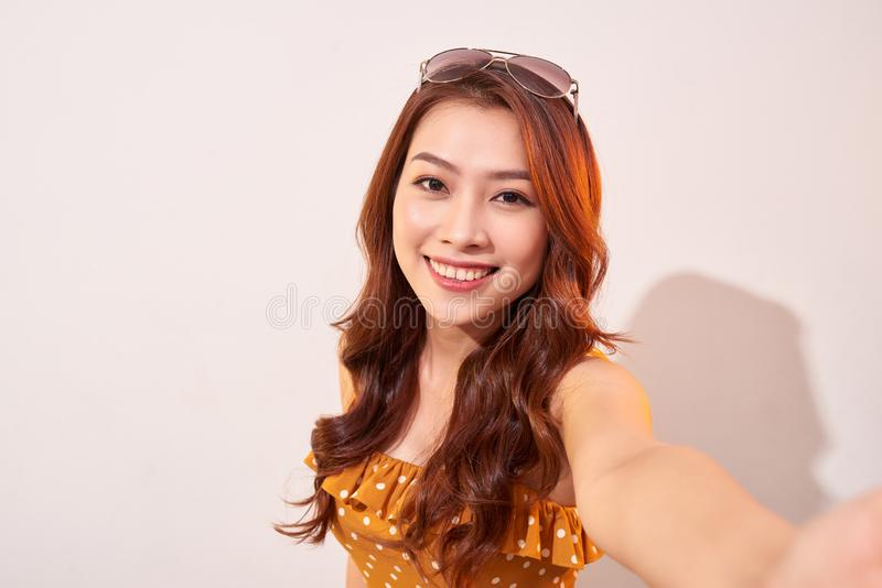 Carefree, careless concept. Young girl take selfie on front camera of modern smartphone wear in summer dress and beaming toothy stock photos