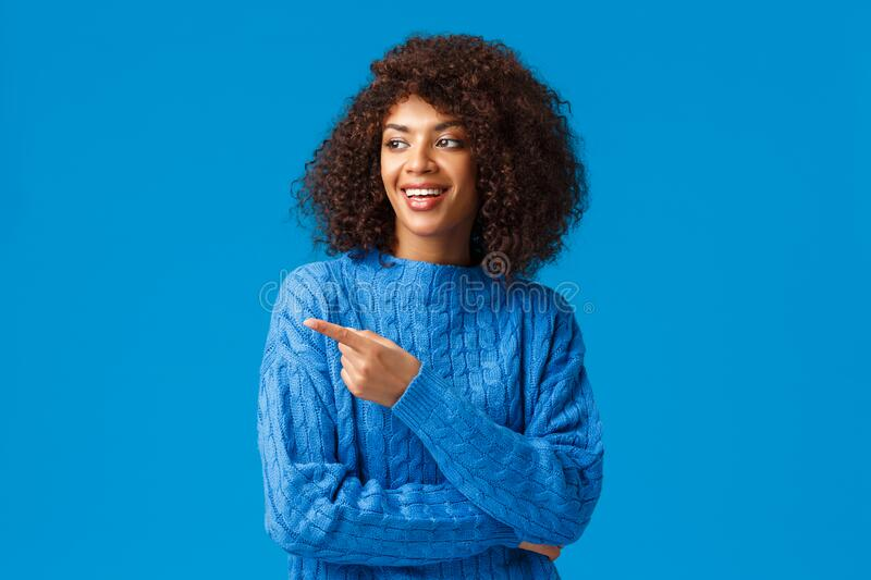 Carefree charismatic african-american lovely female tourist, travel mountain ski resort, winter holidays, pointing. Finger left at funny boyfriend fool around royalty free stock image