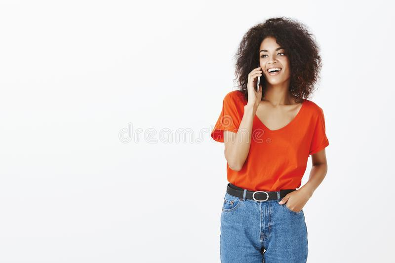 Carefree charming dark-skinned girlfriend in trendy t-shirt and jeans holding hand in pocket while smiling broadly stock photography