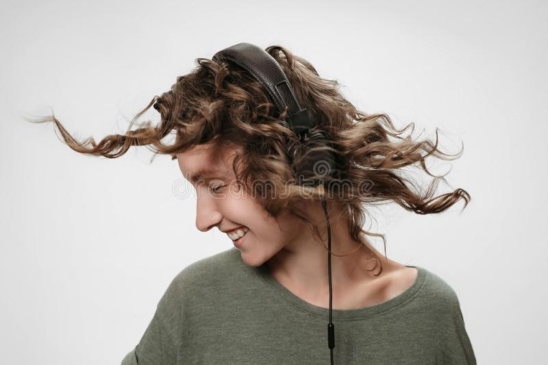 Carefree cheerful young curly woman listen favourite music. With herstereo headphones, smiles positively, being in high spirit, dance, shakes curls, feels royalty free stock photo