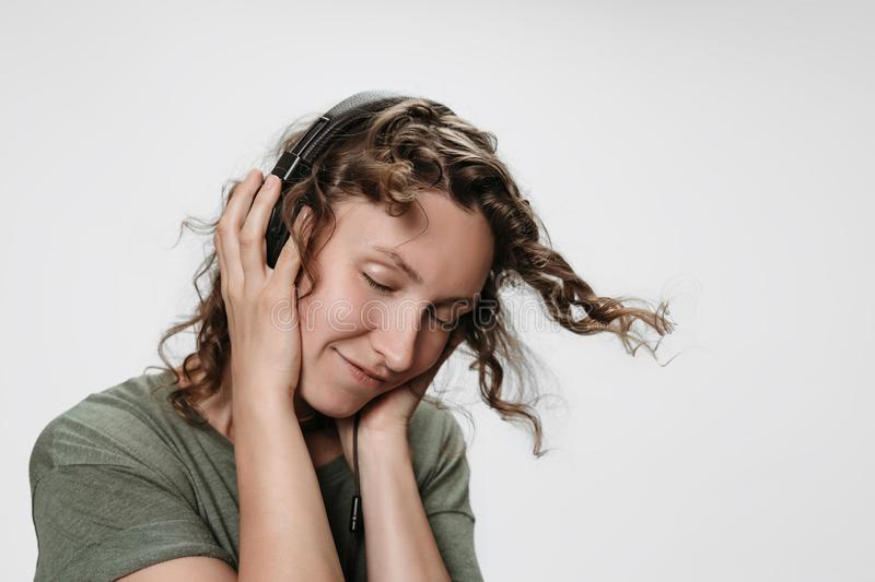 Carefree cheerful young curly woman listen favourite music with hand on her headphones. Smiles positively, dance actively shakes curls, enjoy music. Isolated stock image