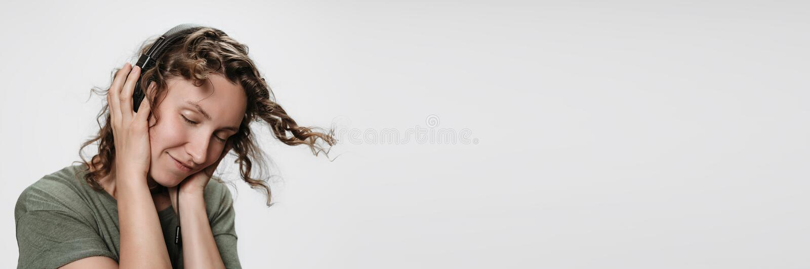 Carefree cheerful young curly woman listen favourite music with her stereo headphones. Carefree cheerful curly woman listen favourite music with her stereo stock photo