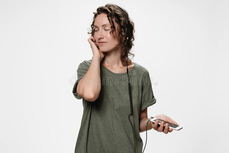 Carefree cheerful young curly woman listen favourite music. Keeps hand on her headphones, satisfied with quality of sound, smiles, enjoy favourite playlist stock photos