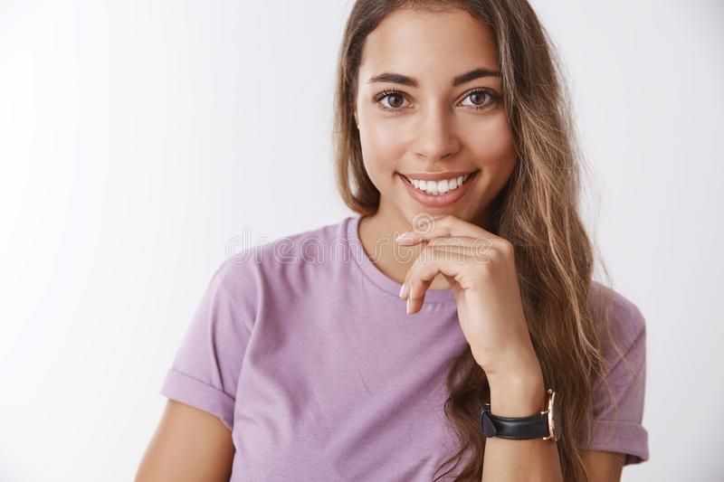 Carefree delighted happy smiling woman curly hair, wearing purple t-shirt, touching smiling pleased, liking hearing. Story, have plan idea, thinking, standing stock photography