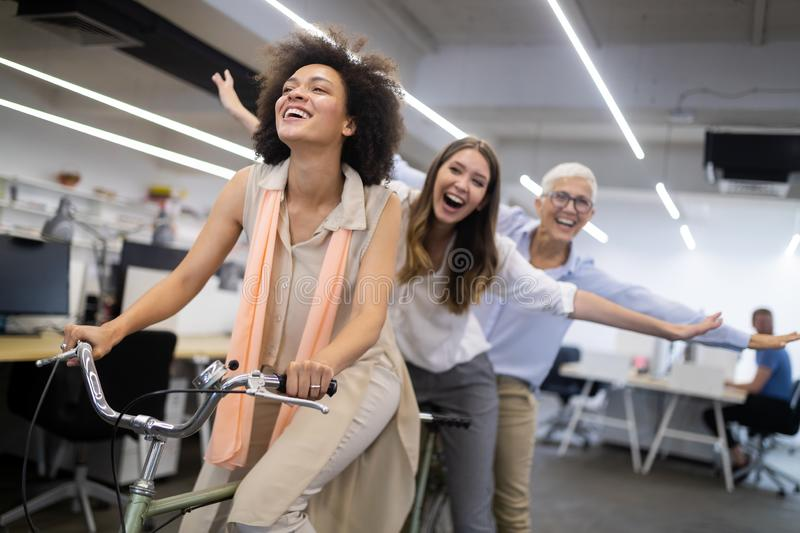 Carefree diverse office workers having fun during work break. Employees coworkers feeling free laughing playing together stock photography