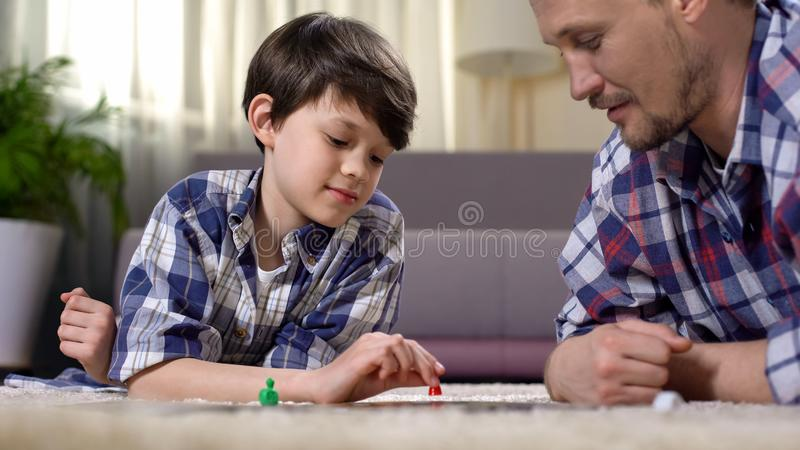 Carefree father and son playing board game, lying on floor, happy family concept stock photography