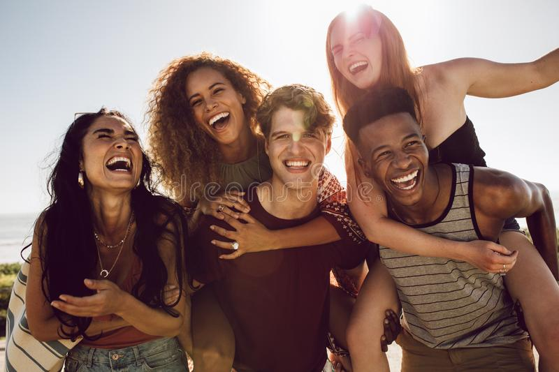 Carefree friends enjoying weekend together. Carefree young friends enjoying weekend together outdoors. Men carrying women in their back and laughing royalty free stock photos