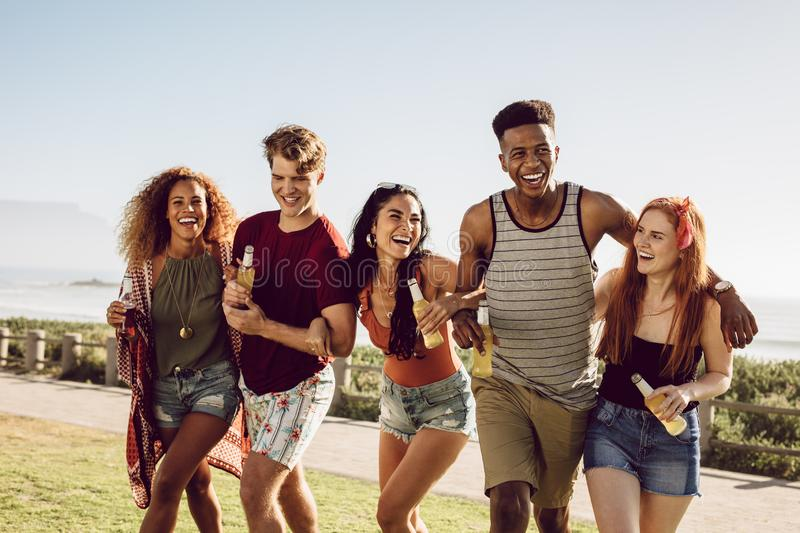 Carefree friends having a great time together. Multi-ethnic group of men and women walking together with locking arms. Young friends lock arms and dancing with royalty free stock photo