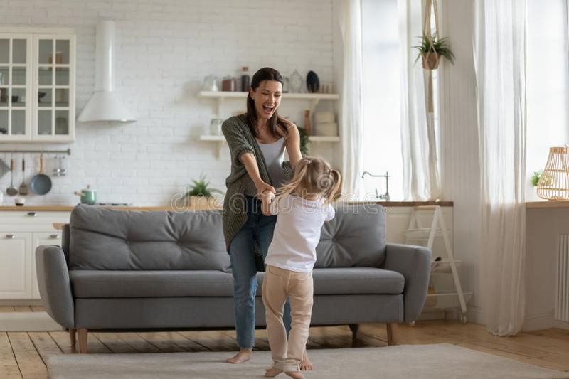 Carefree kid girl having fun with mother dancing in kitchen royalty free stock photos