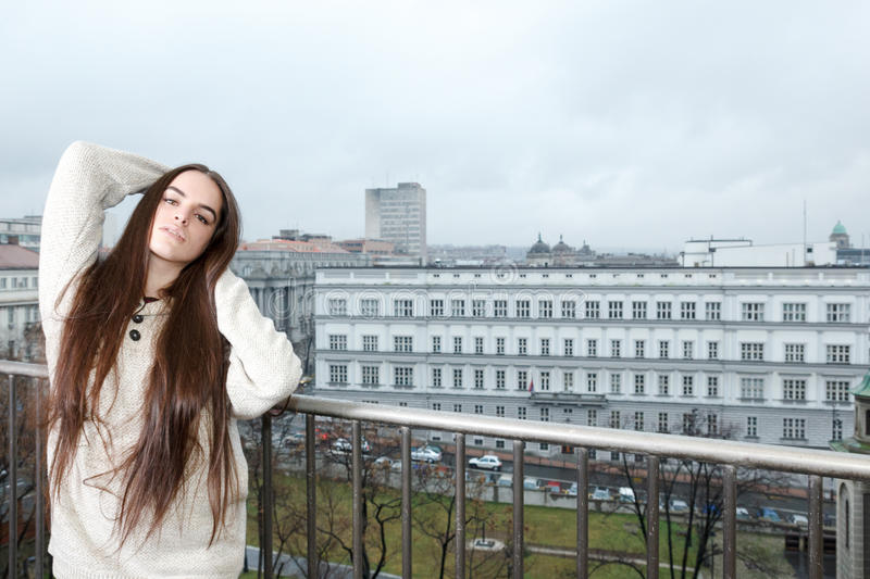 Carefree girl standing on balcony with city in the background. Beautiful carefree girl standing on balcony with city in the background , Young thoughtful woman royalty free stock photo