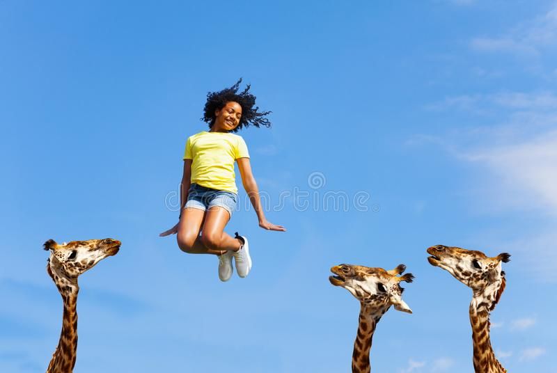 Carefree happy girl jump over giraffes heads royalty free stock photos