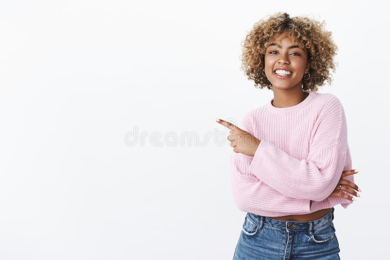 Carefree happy and gorgeous african-american young female student with blond afro haircut smiling and laughing delighted. As pointing at upper left corner stock photography