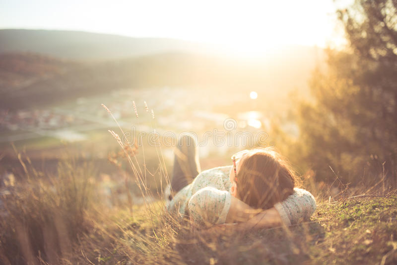 Carefree happy woman lying on green grass meadow on top of mountain edge cliff enjoying sun on her face. Enjoying nature sunset stock image