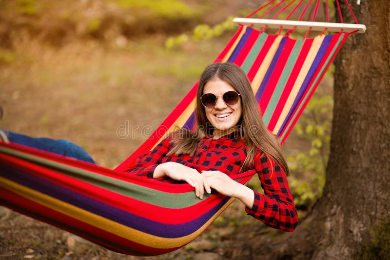 Carefree happy woman lying on hammock enjoying harmony with nature. Freedom. Enjoyment. Relaxing in forest. stock photos