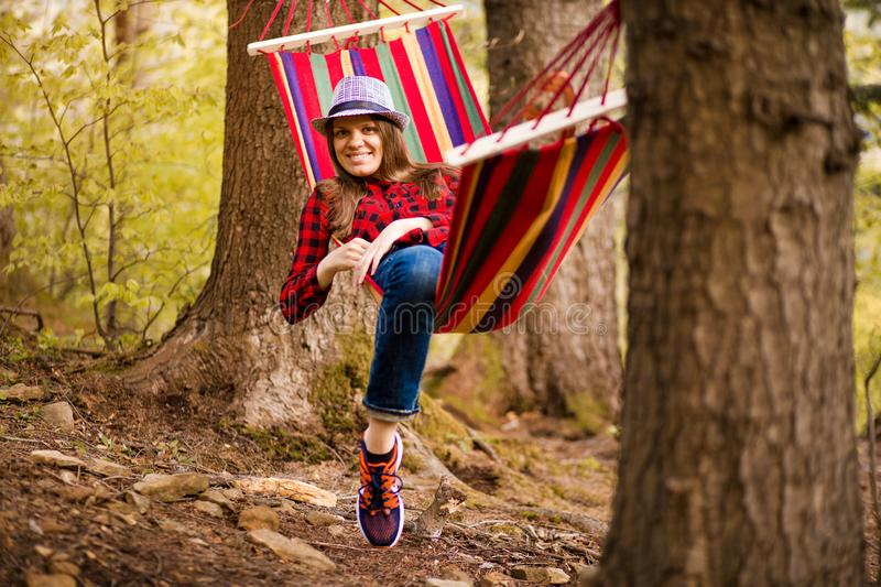 Carefree happy woman lying on hammock enjoying harmony with nature. Freedom. Enjoyment. Relaxing in forest. stock photography