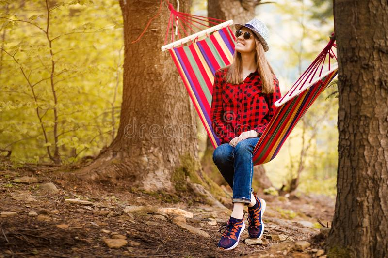 Carefree happy woman lying on hammock enjoying harmony with nature. Freedom. Enjoyment. Relaxing in forest. royalty free stock photography