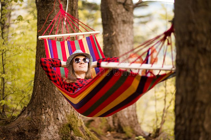 Carefree happy woman lying on hammock enjoying harmony with nature. Freedom. Enjoyment. Relaxing in forest. royalty free stock image