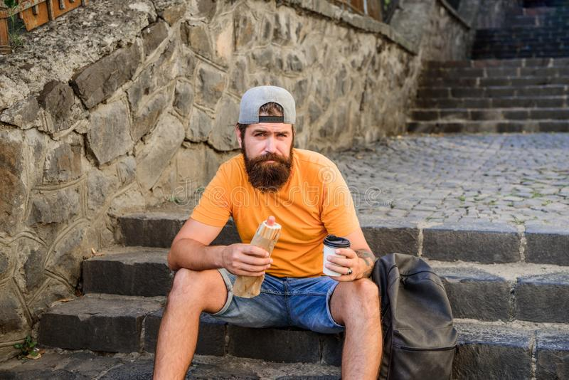 Carefree hipster eat junk food while sit on stairs. Hungry man snack. Junk food. Guy eating hot dog. Man bearded enjoy royalty free stock photography