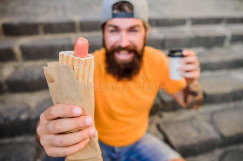 Carefree hipster eat junk food while sit on stairs. Hungry man snack. Guy eating hot dog. Man bearded bite tasty sausage royalty free stock photography