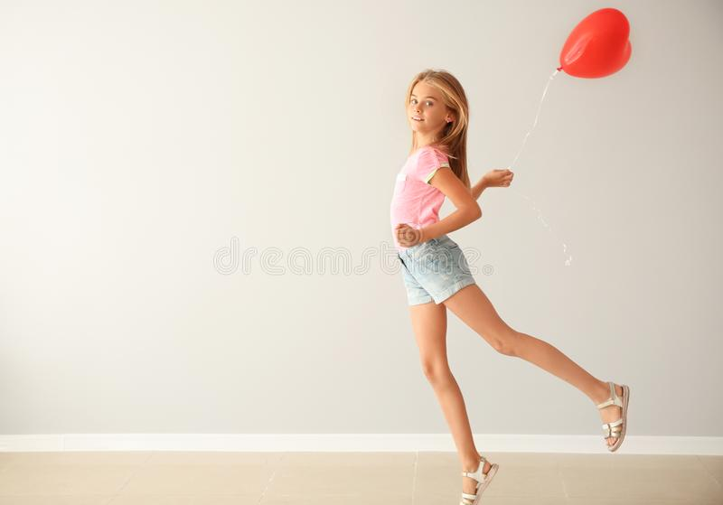 Carefree little girl with heart-shaped air balloon against white wall stock photography